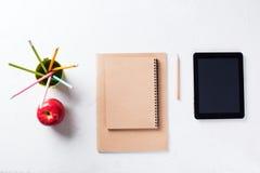Τα χαρτικά γραφείων αντιτίθενται σημειωματάριο της Apple μολυβιών Στοκ Εικόνες