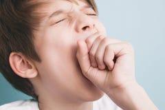Τα χασμουρητά αγοριών ευρέως με τα μάτια του έκλεισαν, καλύπτοντας το στόμα του με την πυγμή του στοκ φωτογραφία με δικαίωμα ελεύθερης χρήσης