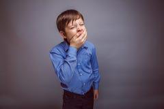 Τα χασμουρητά αγοριών εφήβων θέλουν να κοιμηθούν σε γκρίζο Στοκ Εικόνες