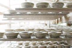 Τα χειροποίητα άσπρα δοχεία αργίλου ξεραίνουν στις ξύλινες σανίδες Εργαστήριο, manufactory στοκ φωτογραφία