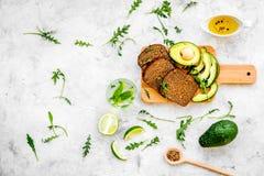 Τα χορτοφάγα σάντουιτς προγευμάτων με το αβοκάντο και τη σίκαλη πασπαλίζουν στο γκρίζο υπόβαθρο τη τοπ άποψη με ψίχουλα στοκ φωτογραφία
