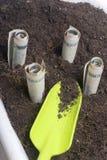 Τα χρήματα αυξάνονται από το έδαφος σε ένα δοχείο λουλουδιών Λογαριασμοί εγγράφου, που διπλώνονται σε έναν σωλήνα, ραβδί από το έ Στοκ Εικόνες