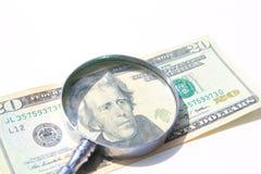 τα χρήματα ενισχύουν κάτω το γυαλί που απομονώνεται Στοκ Εικόνα