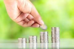 Τα χρήματα που συλλέγουν τα ασημένια νομίσματα που προσθέτουν τα χέρια ατόμων ` s χρημάτων αυξάνουν την ανάπτυξη χρημάτων του υπο Στοκ Εικόνα