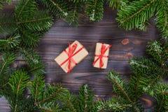 Τα χριστουγεννιάτικα δώρα με την κόκκινη κορδέλλα στο σκοτεινό ξύλινο υπόβαθρο σε ένα πλαίσιο φιαγμένο από έλατο διακλαδίζονται μ Στοκ φωτογραφία με δικαίωμα ελεύθερης χρήσης