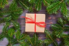 Τα χριστουγεννιάτικα δώρα με την κόκκινη κορδέλλα στο σκοτεινό ξύλινο υπόβαθρο σε ένα πλαίσιο φιαγμένο από έλατο διακλαδίζονται μ Στοκ φωτογραφίες με δικαίωμα ελεύθερης χρήσης