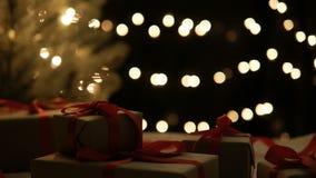Τα χριστουγεννιάτικα δώρα με το υπόβαθρο φω'των μετακινούνται τον πυροβολισμό φιλμ μικρού μήκους