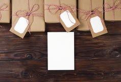 Τα χριστουγεννιάτικα δώρα με τα lables στην ξύλινη τοπ άποψη υποβάθρου, επίπεδη βάζουν Έννοια δώρων Χριστουγέννων, διάστημα κειμέ Στοκ Φωτογραφία
