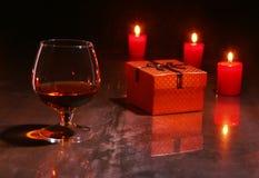 τα Χριστούγεννα διακοσμούν τις φρέσκες βασικές ιδέες διακοσμήσεων ποτήρι του κονιάκ ή του ουίσκυ, κόκκινα κεριά και κιβώτιο δώρων στοκ εικόνες