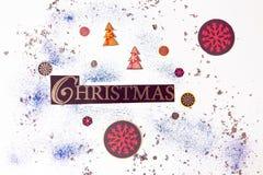 Τα Χριστούγεννα επιγραφής σε ένα άσπρο υπόβαθρο περιβάλλονται από τις εορταστικές, χειμερινές ιδιότητες Υπέροχα σχεδιασμένος σε έ στοκ εικόνα με δικαίωμα ελεύθερης χρήσης