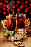 Τα Χριστούγεννα θέρμαναν το κόκκινο κρασί με την προσθήκη των καρυκευμάτων και των πορτοκαλιών Στοκ Εικόνες