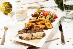 τα Χριστούγεννα διακοσμούν τις φρέσκες βασικές ιδέες γευμάτων Μπριζόλα βόειου κρέατος με τις ψημένες πατάτες Στοκ Εικόνα