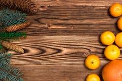 Τα Χριστούγεννα και τα νέα μανταρίνια έτους δίπλα στο χριστουγεννιάτικο δέντρο διακλαδίζονται με τους κώνους σε ένα ξύλινο υπόβαθ στοκ φωτογραφία