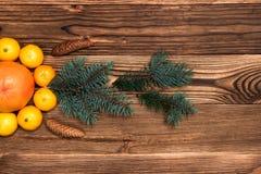 Τα Χριστούγεννα και τα νέα μανταρίνια έτους δίπλα στο χριστουγεννιάτικο δέντρο διακλαδίζονται με τους κώνους σε ένα ξύλινο υπόβαθ στοκ εικόνες