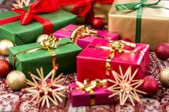 Τα Χριστούγεννα παρουσιάζουν με τα τόξα, τα μπιχλιμπίδια και τα αστέρια στοκ εικόνες