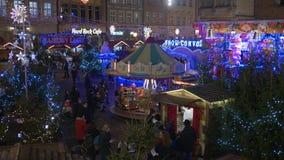Τα Χριστούγεννα στην Ευρώπη, τουρίστες περπατούν στην αγορά Χριστουγέννων που περνά τη νύχτα από τα φωτισμένα περίπτερα απόθεμα βίντεο