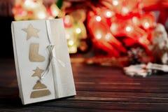 Τα Χριστούγεννα τύλιξαν το παρόν κιβώτιο στο υπόβαθρο της θερμής γιρλάντας ligh Στοκ Εικόνες