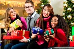 Τα Χριστούγεννα φίλων που ψωνίζουν με παρουσιάζουν στη λεωφόρο Στοκ εικόνες με δικαίωμα ελεύθερης χρήσης