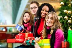 Τα Χριστούγεννα φίλων που ψωνίζουν με παρουσιάζουν στη λεωφόρο Στοκ φωτογραφία με δικαίωμα ελεύθερης χρήσης