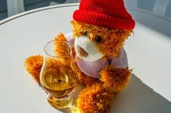 Τα Χριστούγεννα teddy αντέχουν με το ποτήρι του ενιαίου ουίσκυ βύνης, σύμβολο ο Στοκ Φωτογραφίες
