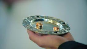 Τα χρυσά δαχτυλίδια βρίσκονται σε ένα ασημένιο πιάτο, σύζυγος χεριών φιλμ μικρού μήκους