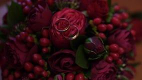 Τα χρυσά γαμήλια δαχτυλίδια ζυγίζουν σε μια ανθοδέσμη των τριαντάφυλλων φιλμ μικρού μήκους