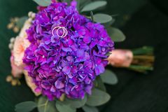 Τα χρυσά γαμήλια δαχτυλίδια στην ανθοδέσμη του πορφυρού hydrangea, ρόδινα τριαντάφυλλα ανθίζουν με τις ιώδεις κορδέλλες στο αγροτ στοκ φωτογραφίες