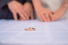 Τα χρυσά γαμήλια δαχτυλίδια βρίσκονται στον πίνακα πίσω από τους θόλωσαν τα χέρια των newlyweds Χέρι νυφών με το δαχτυλίδι μια αν στοκ εικόνες