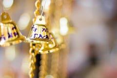 Τα χρυσά κουδούνια Χριστουγέννων που κρεμούν ως νέα παιχνίδια έτους το υπόβαθρο Στοκ Φωτογραφίες