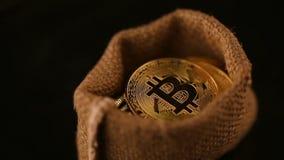 Τα χρυσά νομίσματα bitcoin στην τσάντα περιστρέφονται στο μαύρο υπόβαθρο φιλμ μικρού μήκους