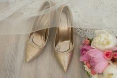 Τα χρυσά νυφικά παπούτσια καλύπτονται με ένα πέπλο Στοκ εικόνα με δικαίωμα ελεύθερης χρήσης