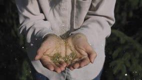 Τα χρυσά σπινθηρίσματα φυσιούνται μακριά στα χέρια ενός νέου κοριτσιού απόθεμα βίντεο