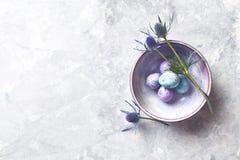Τα χρωματισμένα αυγά ορτυκιών και τα λουλούδια ελαιόπρινου θάλασσας σε ένα κεραμικό επίπεδο κύπελλων βάζουν τη ρύθμιση στοκ φωτογραφία
