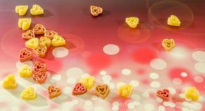 Τα χρωματισμένα (κόκκινο, κίτρινο ένα πορτοκάλι) ζυμαρικά μορφής καρδιών, χρωματισμένο υπόβαθρο degradee bokeh, κλείνουν επάνω Στοκ Φωτογραφία