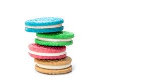 Τα χρωματισμένα μπισκότα πλήρωσης κρέμας συσσώρευσαν απομονωμένος στο άσπρο backgrou Στοκ Εικόνες