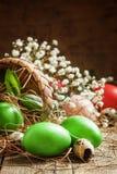 Τα χρωματισμένα πράσινα αυγά Πάσχας που χύνονται τα υφαμένα καλάθια φλοιών σημύδων στο στρεπτόκοκκο στοκ εικόνα