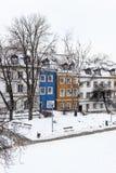 Τα χρωματισμένα σπίτια στην παλαιά πόλη της Βαρσοβίας μετά από το χιόνι μαίνονται το χειμώνα, ζωηρόχρωμα εξωτερικά ενάντια στο άσ στοκ εικόνα