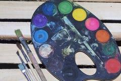 Τα χρώματα και οι βούρτσες χρωμάτων βρίσκονται σε μια ξύλινη σανίδα των πινάκων Στοκ Εικόνες