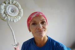 Τα χρώματα κοριτσιών ασπρίζουν ένα ανώτατο όριο, επισκευάζουν το διαμέρισμα με το χ του Στοκ Φωτογραφία