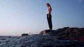 Τα χτυπήματα αέρα σε ένα κορίτσι, στις πέτρες στη θάλασσα, οι παφλασμοί παίρνουν στη κάμερα, αφρός από τα κύματα απόθεμα βίντεο