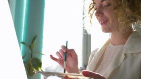 Τα χόμπι καλλιτεχνών, ευτυχές όμορφο κορίτσι ζωγράφων αναμιγνύουν τα χρώματα στην παλέτα με τη λεπτή βούρτσα εργαζόμενο στη νέα ζ απόθεμα βίντεο