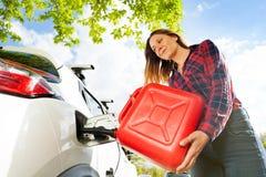 Τα χύνοντας καύσιμα γυναικών στη δεξαμενή αερίου ενός αυτοκινήτου από μπορούν στοκ φωτογραφίες με δικαίωμα ελεύθερης χρήσης