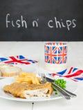 Τα ψάρια και τα τσιπ με ένα φλυτζάνι του τσαγιού πασπαλίζουν με ψίχουλα και βούτυρο και ένωση jac Στοκ Φωτογραφία