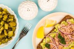 Τα ψάρια και το αβοκάντο τόνου με τα κρεμμύδια στη σίκαλη πασπαλίζουν το ανοικτό πρόσωπο Sandwic με ψίχουλα στοκ φωτογραφία