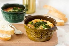 Τα ψημένα ανακατωμένα αυγά με το μπρόκολο, τα λουκάνικα και το τυρί εξυπηρέτησαν με τις φέτες του ψωμιού Αγροτικό ύφος στοκ φωτογραφία