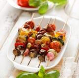 Τα ψημένα στη σχάρα οβελίδια των λαχανικών και του κρέατος σε ένα χορτάρι μαρινάρουν στο άσπρο πιάτο Στοκ Εικόνες