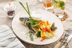 Τα ψημένα στη σχάρα ψάρια dorado γέμισαν με τα διαφορετικά λαχανικά στο άσπρο πιάτο που εξυπηρετήθηκε στον πίνακα στοκ φωτογραφία