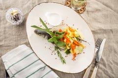 Τα ψημένα στη σχάρα ψάρια dorado γέμισαν με τα διαφορετικά λαχανικά στο άσπρο πιάτο που εξυπηρετήθηκε στον πίνακα στοκ εικόνες
