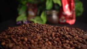 Τα ψημένα φασόλια καφέ πέφτουν κάτω από τα χέρια της Farmer σε έναν μαύρο πίνακα με το υπόβαθρο τροφίμων φιλμ μικρού μήκους