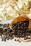 Τα ψημένα φασόλια καφέ διασκόρπισαν από την τσάντα εγγράφου πέρα από το σκούρο γκρι πιάτο γρανίτη, που συλλήφθηκε από τη τοπ άποψ Στοκ εικόνα με δικαίωμα ελεύθερης χρήσης